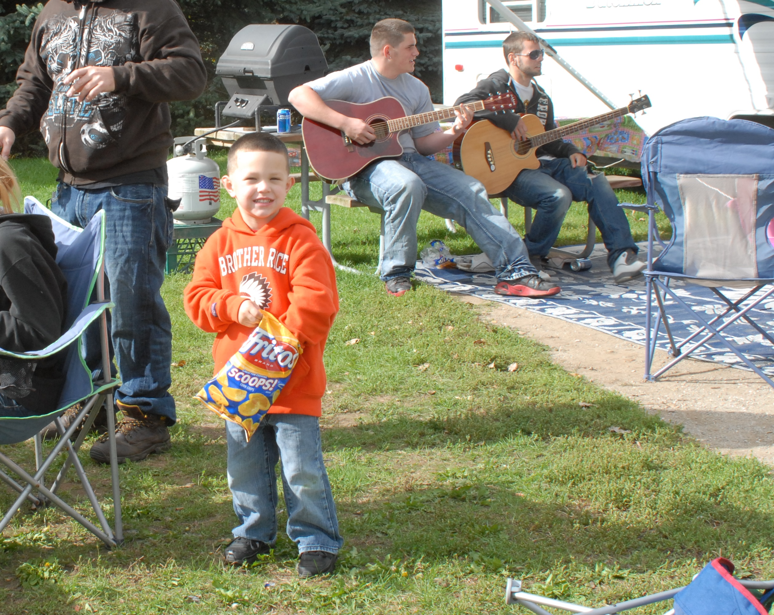 Little boy enjoying chips at the campground while his friends play guitar in the background.