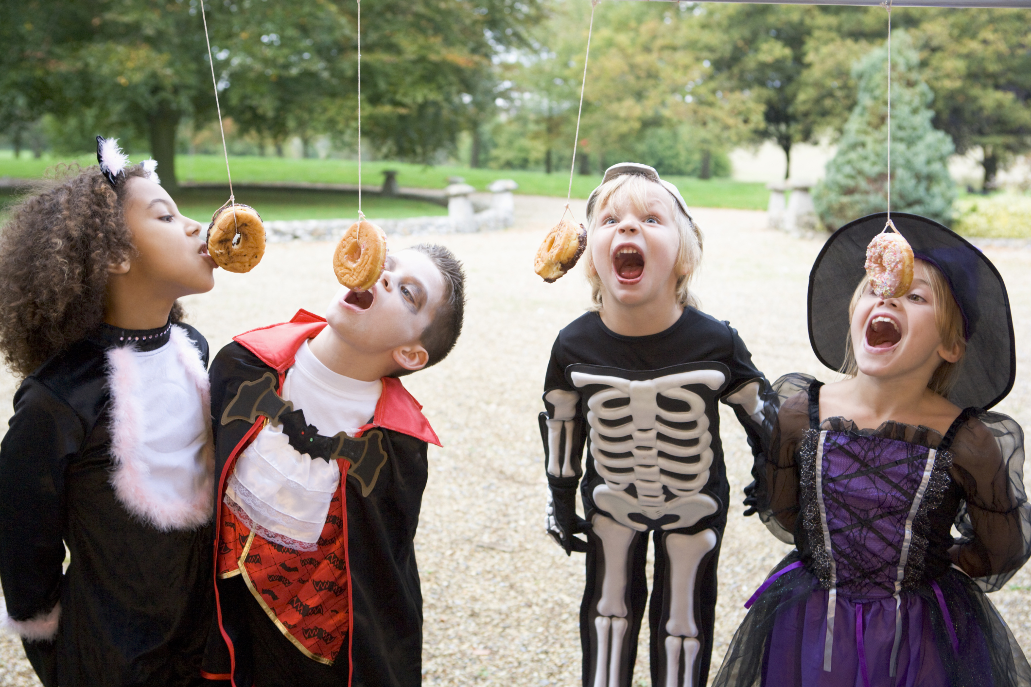 Four young friends on Halloween in costumes eating donuts hanging off strings.