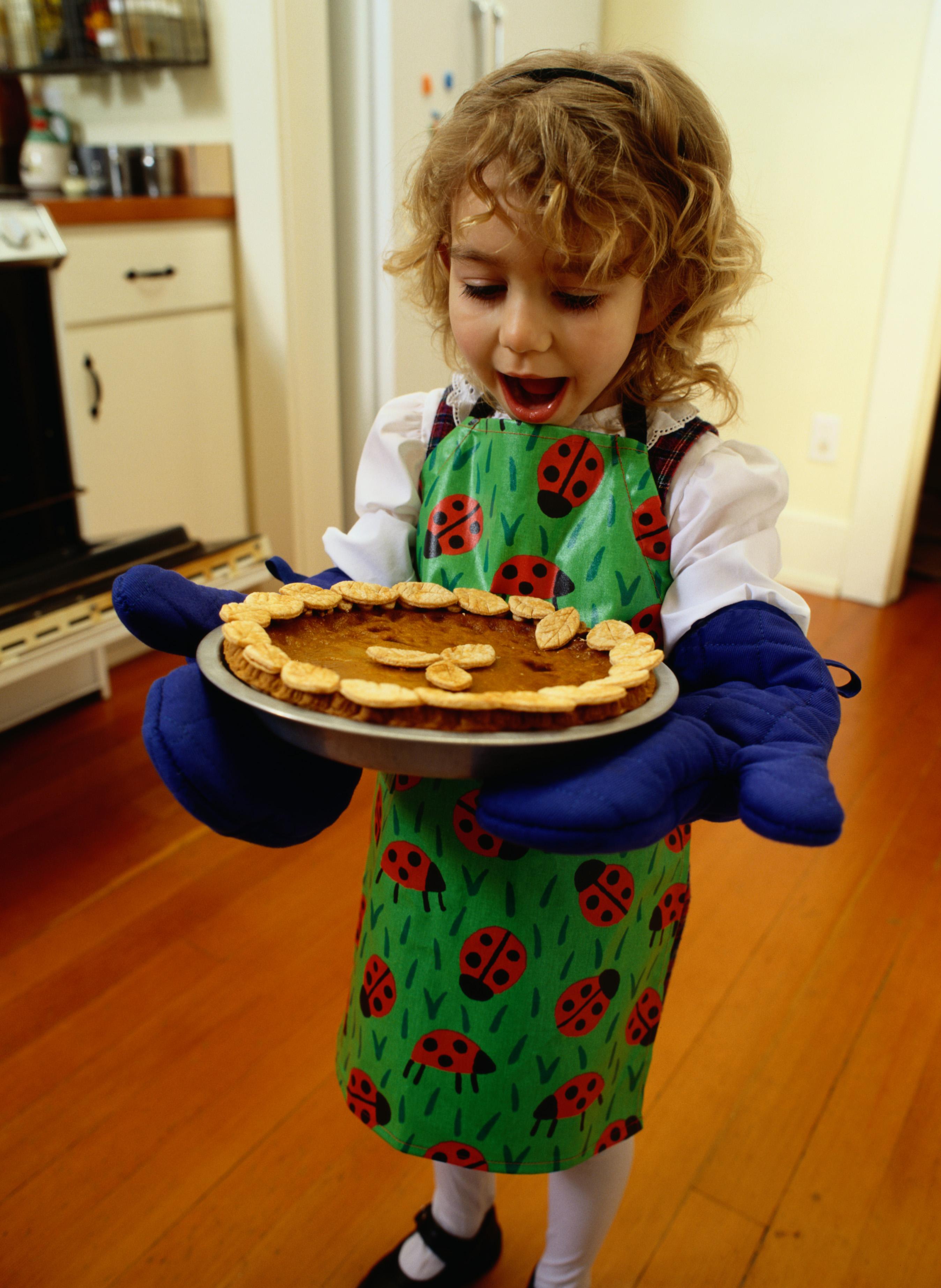 Portrait of a Girl Holding a Hot Pumpkin Pie.