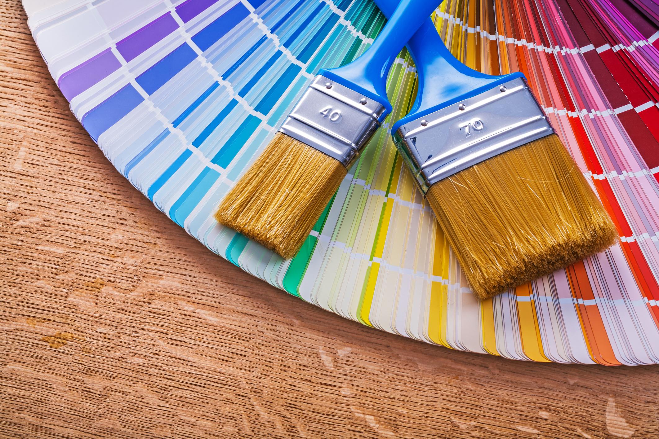 Paint brushes on pantone color palette guide maintenance concept.