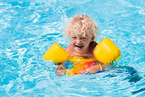 Happy little boy in swimming pool