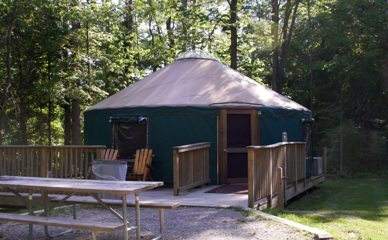 A campsite with a dark green yurt with a tan top sits in the middle of this scene. It is surrounded by trees with green foliage and has a two wooden chairs and a picnic table in front.