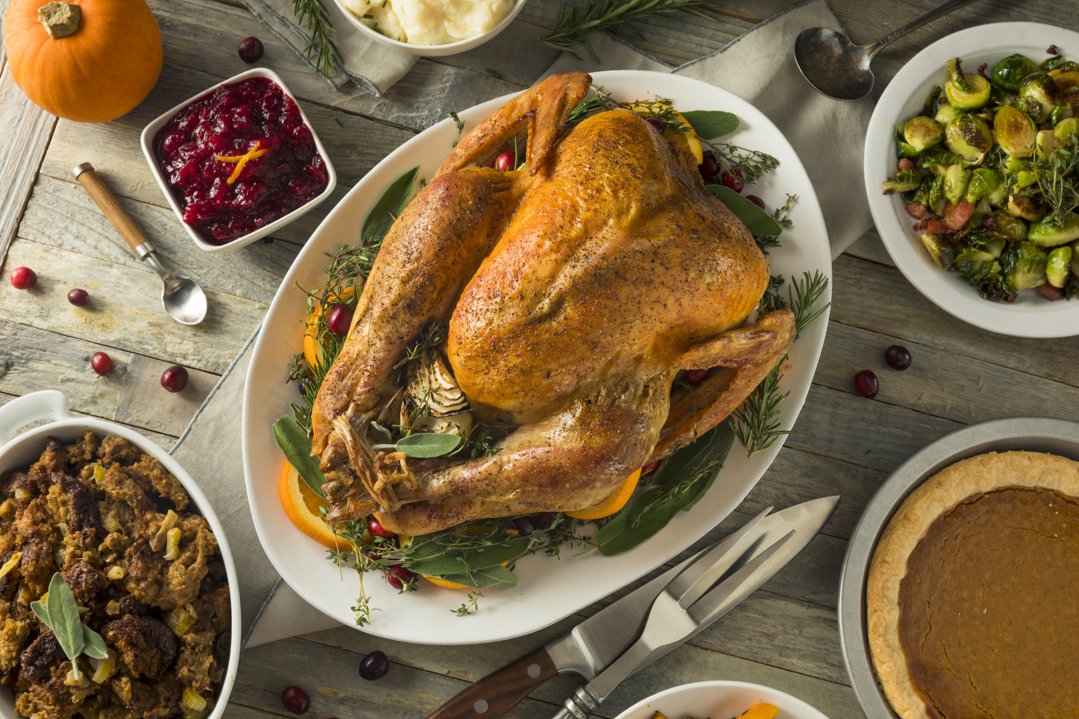 A beautiful, cooked turkey sits in the center of the table amidst of Thanksgiving dishes like stuffing and cranberry sauce.