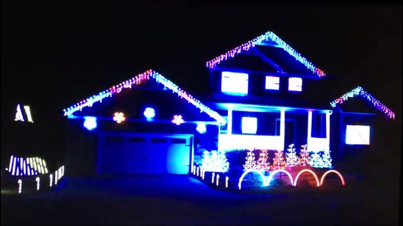 House decorated in red, blue, and purple flashing lights. Most of the house is illuminated in a bright, blue glow.