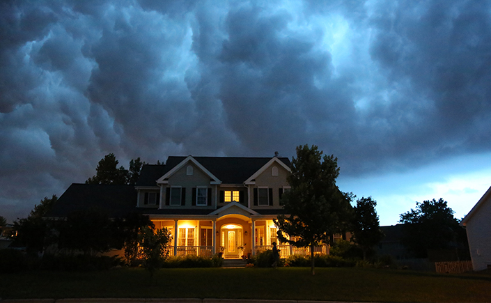 A large two-story home with large, moving clouds above it. The sky is darkening and it appears that bad weather is on its way.