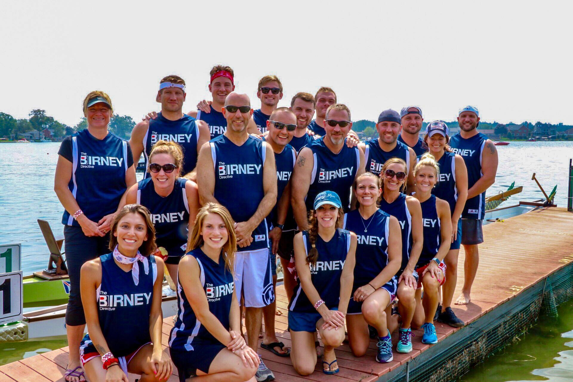 The Birney Directive Dragon Boat Racing Teams poses for a photo at the 2018 Dragon on the Lake Festival. Racers are positioned in three rows on a dock and wearing sleeveless blue muscle shirts.