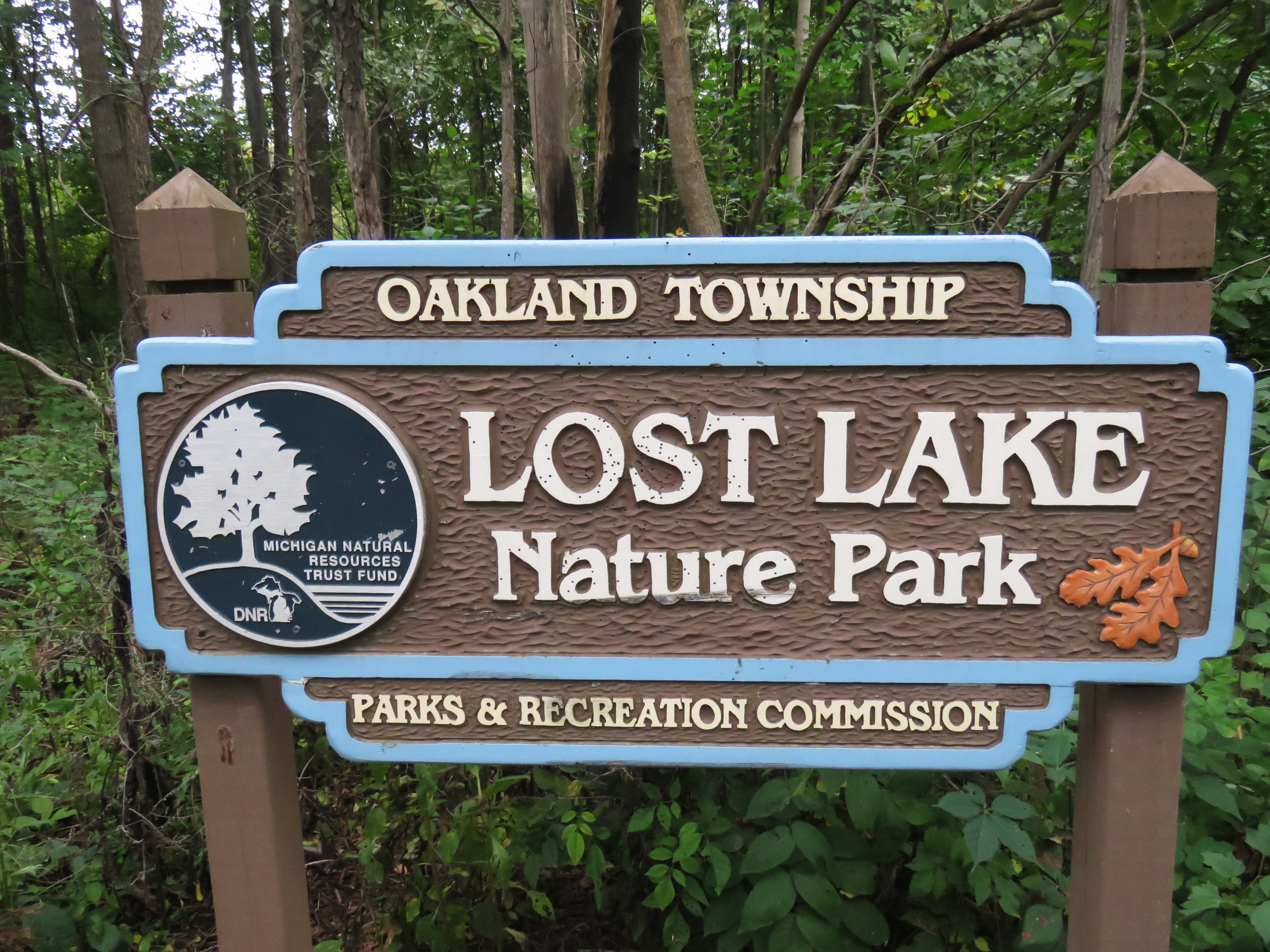 A brown wooden sign stands in front of trees and plants with green foliage. The sign says: Oakland Township - Lost Lake Nature Preserve - Parks and Recreation Commission. It has the seal for Michigan Natural Resources Trust Fund to the left of the text. Two rust colored Oak leaves have been placed to the right of the text.