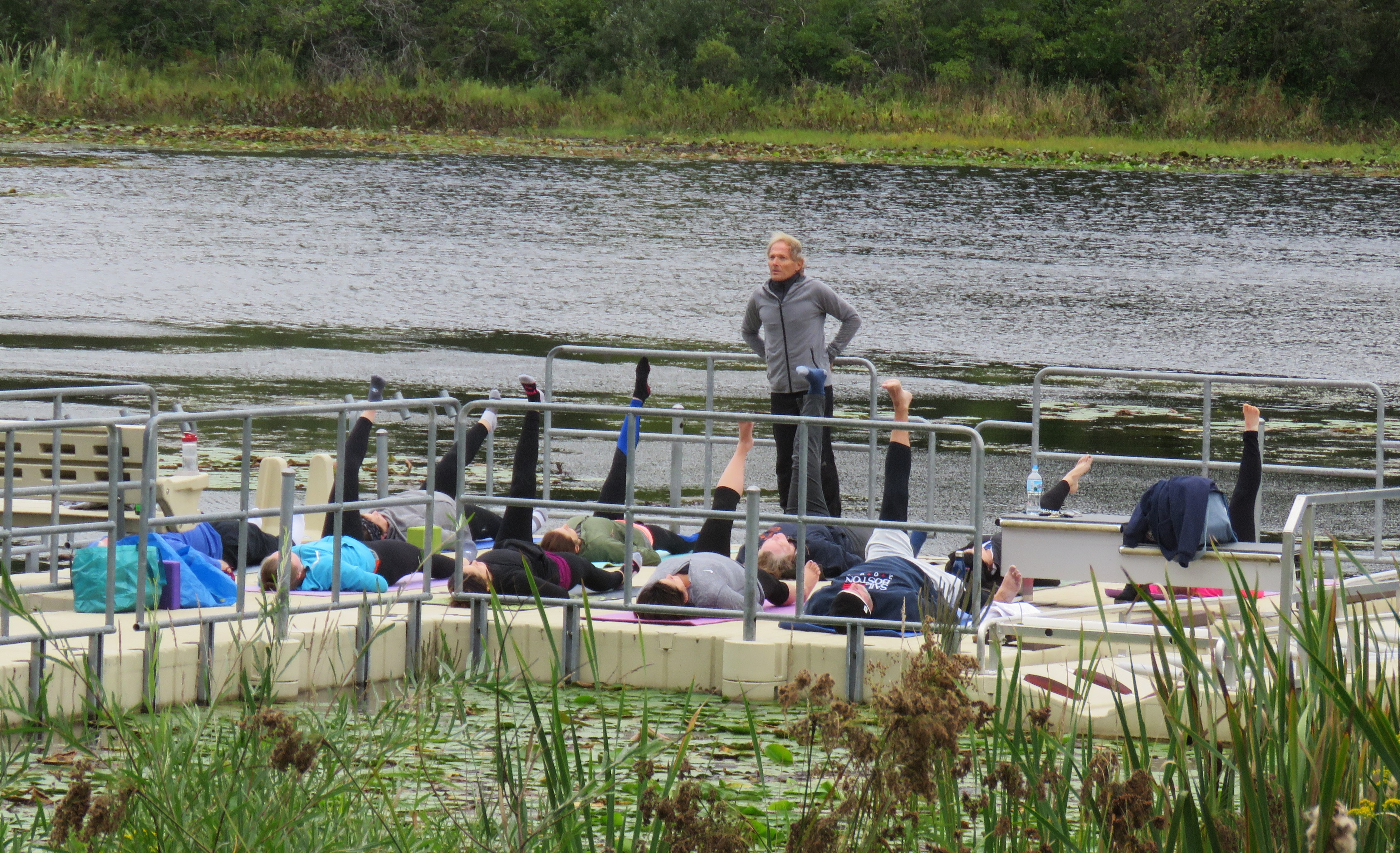 A fitness instructor stands on a dock at Lost Lake Nature Preserve while class attendees practice yoga on mats spread along the dock.