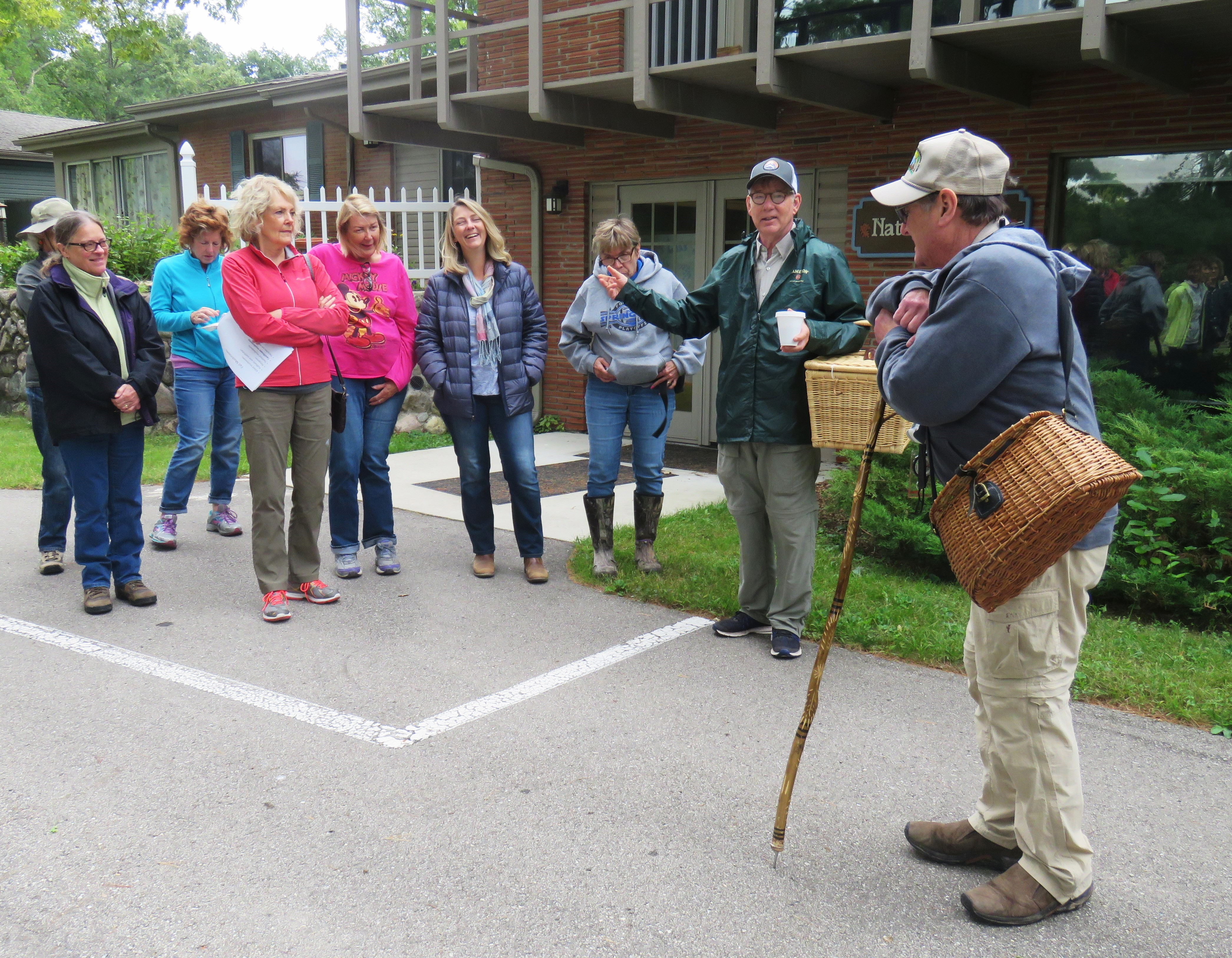 A group of mushroom foragers stands outside of a nature center talking.