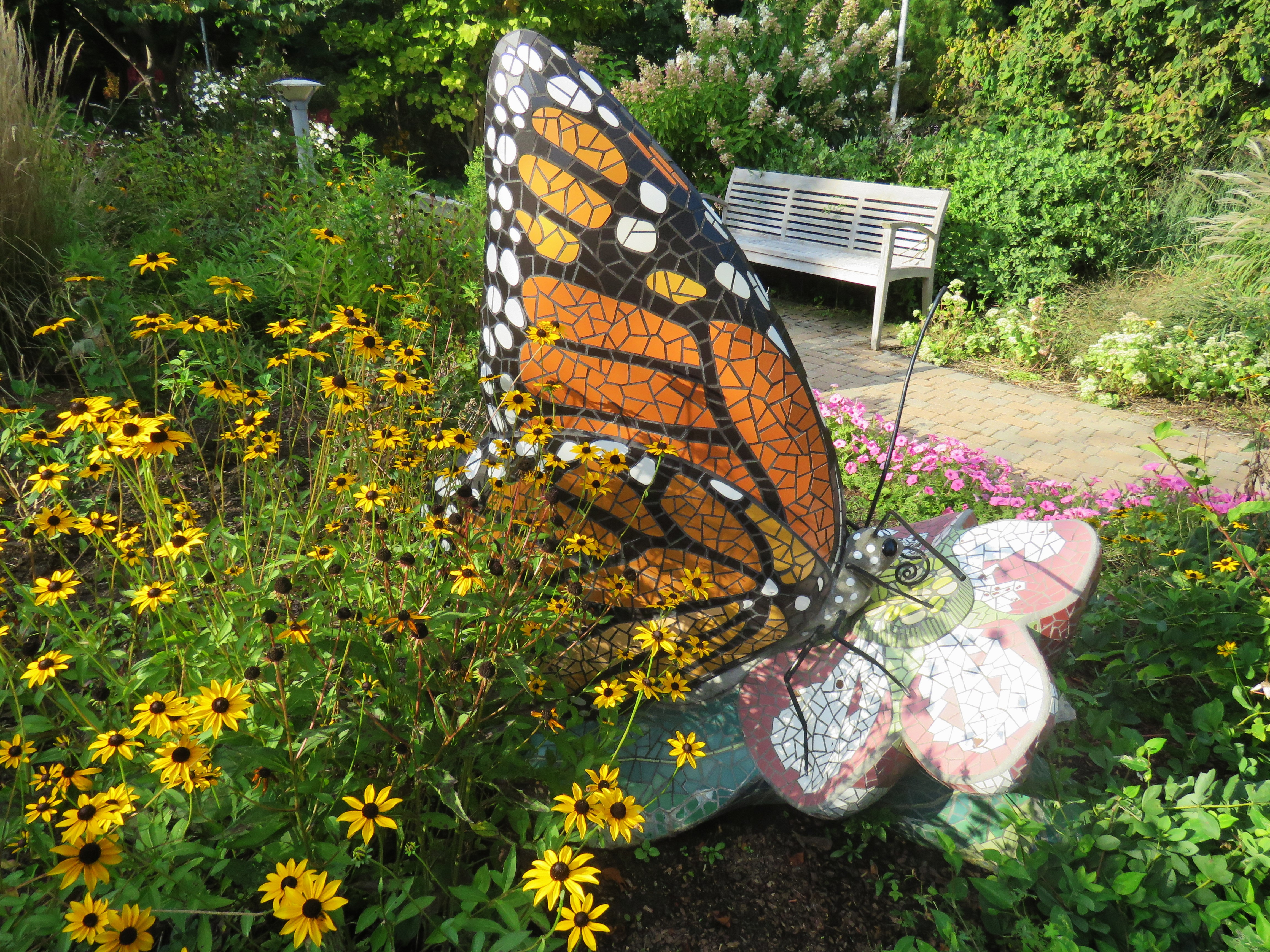 A large sculpture of a monarch butterfly crafted from a mosaic of tiles sits in the midst of a garden. A bench stands in the background near a brick paver path. Black-eyed susans and other plants surround the sculpture.