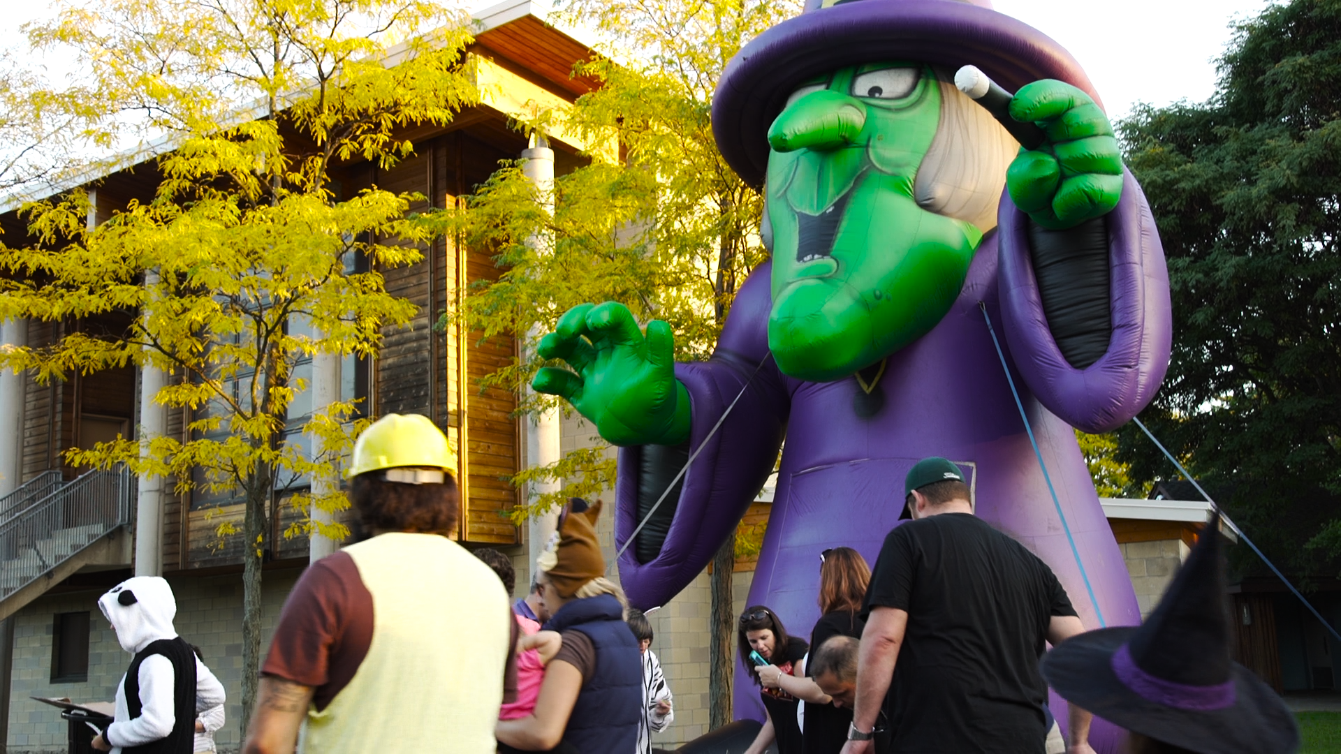 """Families, some dressed in Halloween costumes walk down the Trick or Treat Trail at the Detroit Zoo's """"Zoo Boo"""" An inflatable witch stand in the background next to a tree with yellow leaves."""