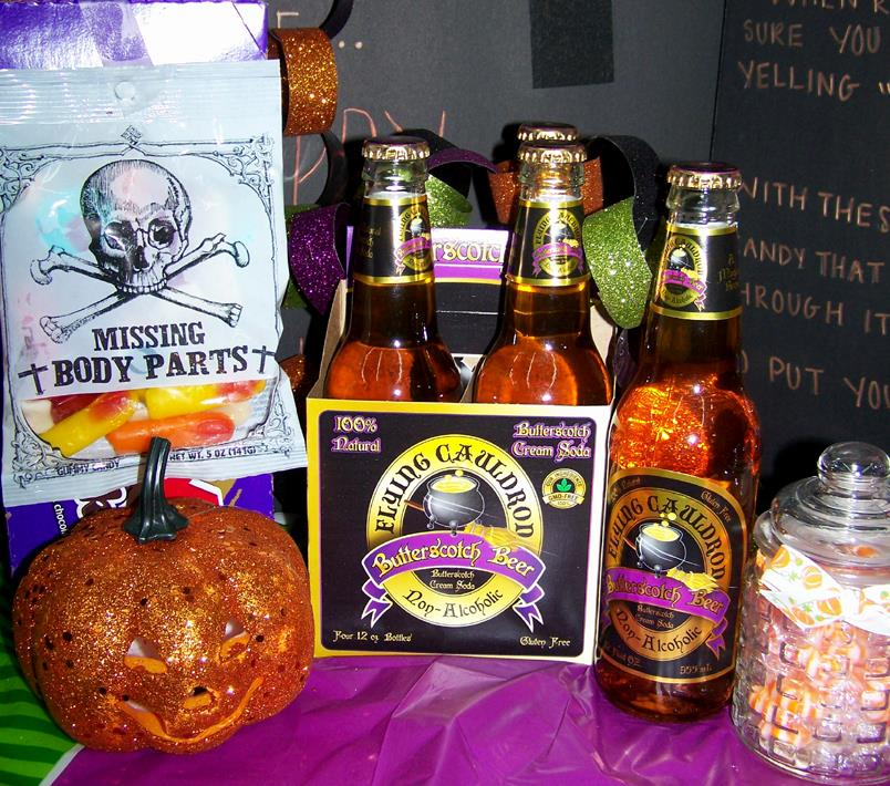 A table set with Halloween candy and decorations. A four-pack of Butterscotch Beer Cream Soda sits in the middle. A small orange jack o' lantern a bag of gummy candy (labeled Missing Body Parts with a Skull and Crossbones) sit to the left of the sodas. A glass jar filled with orange and white candy sits to the right of the soda.
