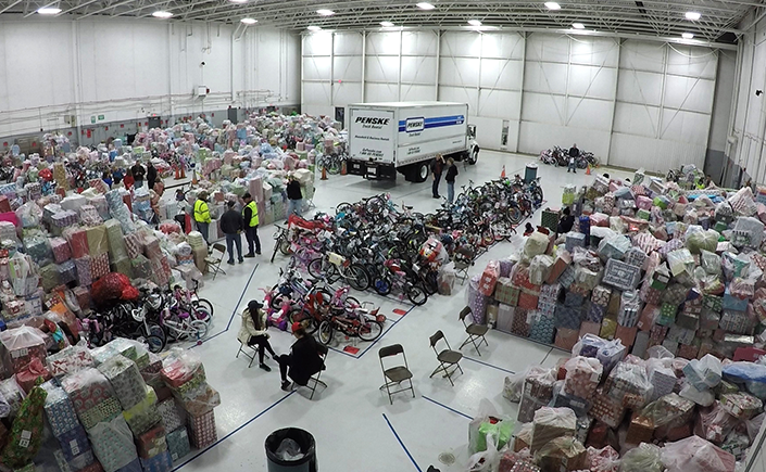 An airplane hanger is filled with mountains of wrapped gifts and dozens of bicycles waiting to be loaded into airplanes for Operation Good Cheer.