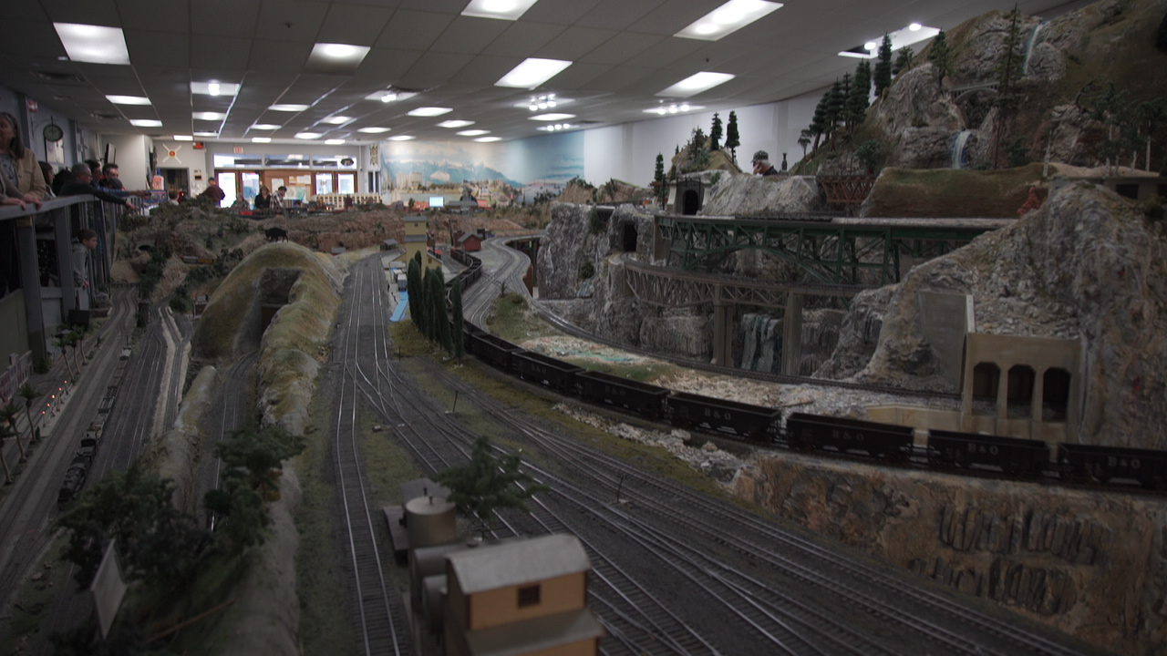People gaze upon a miniature depiction of a mountainside highway and railroad town.