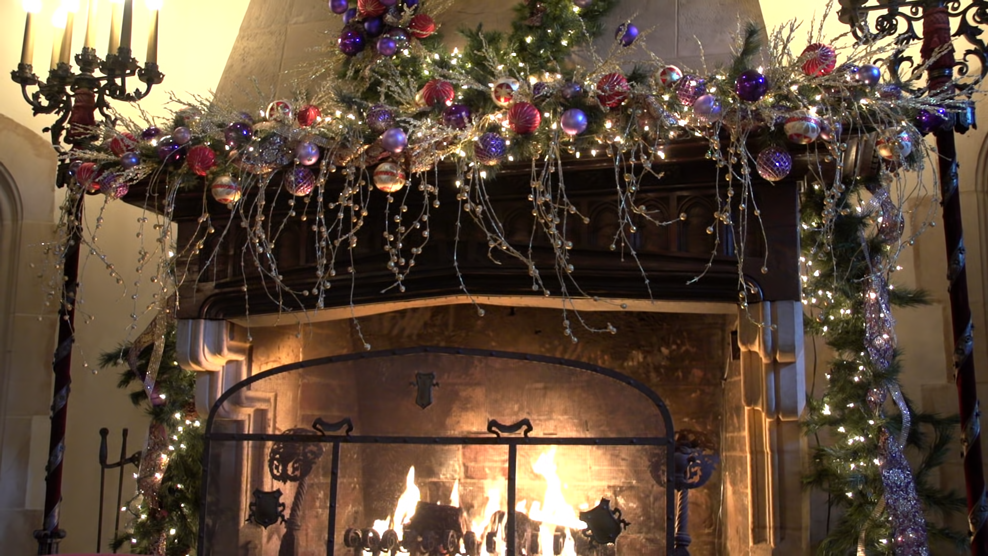Festive bulbs and sparkling lights hang over a crackling, wood fireplace in a decorated living room.