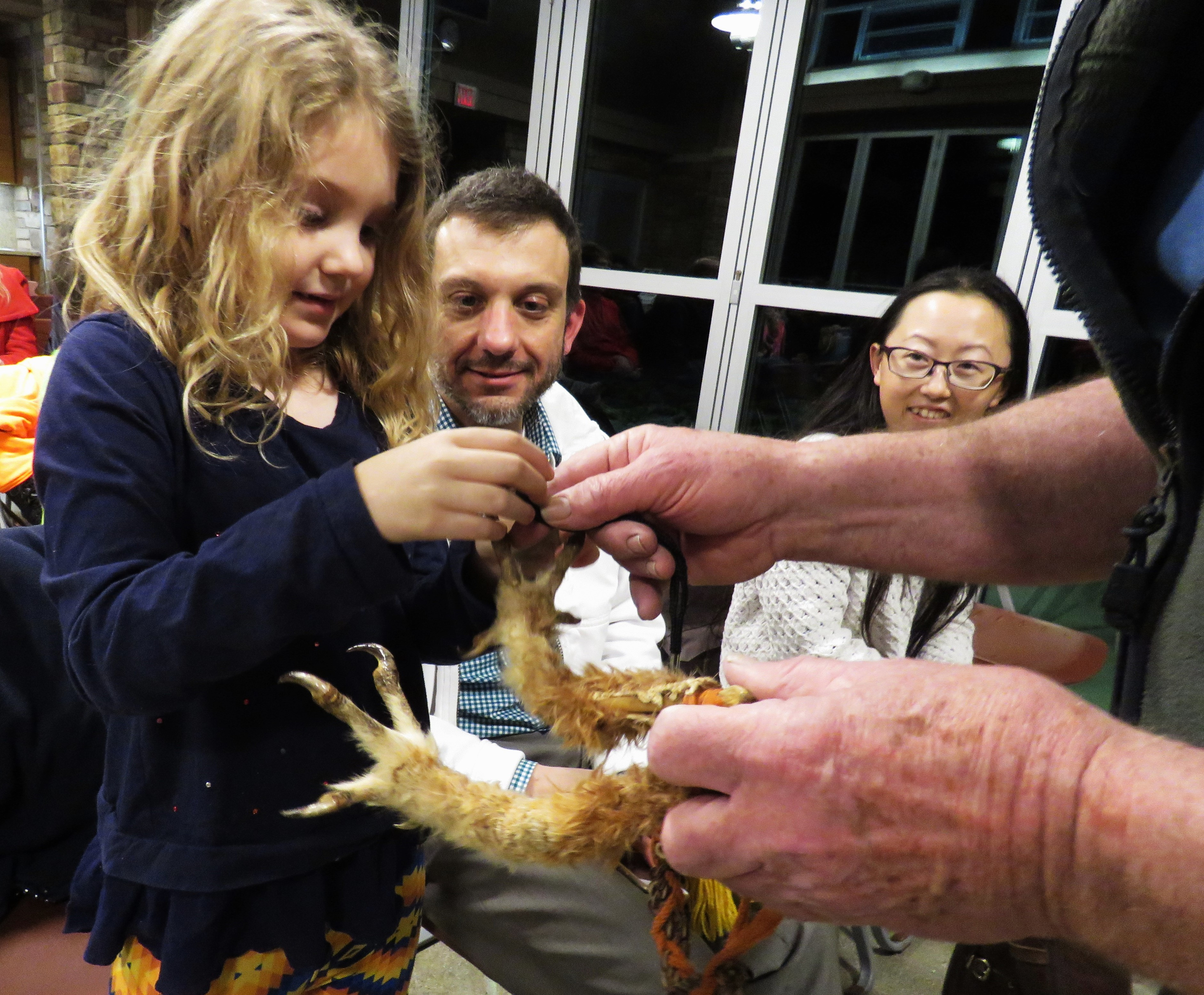A young girl touches the talon of a great horned owl.