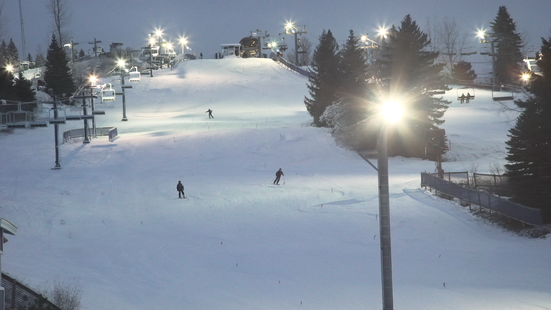Three skiers ride down Mt. Holly in a dark Michigan night lit up by the lights of the resort.