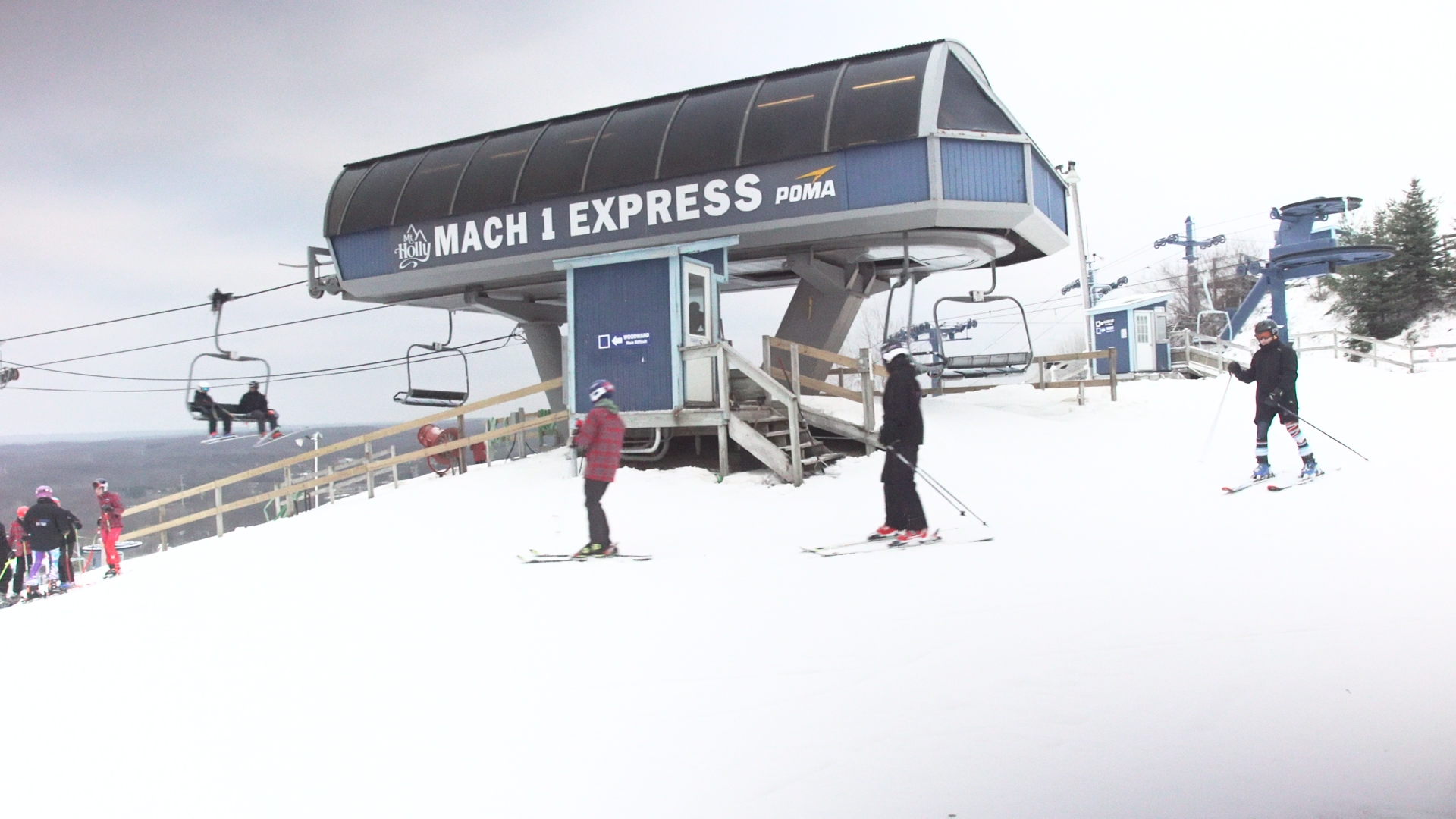 Skiers prepare to ride the slopes beside the Mach 1 Express, Southeastern Michigan's only high-speed detachable chairlift.