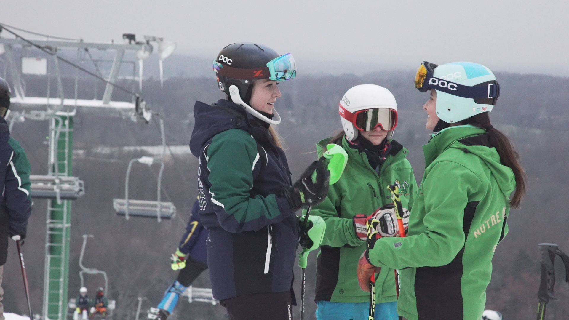 Three high school girls ski racing team members talk at the top of the slope.