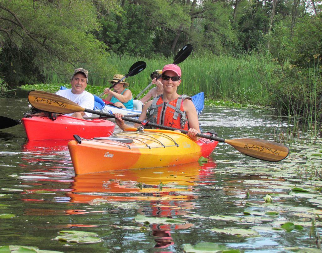 Smiling kayakers on water