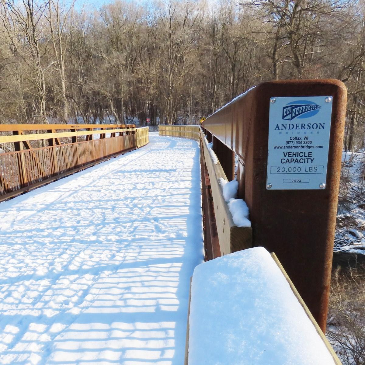 The Van Tassel Bridge covered in snow. The builder's sign (Anderson Bridges) is posted on the bridge's steel post.