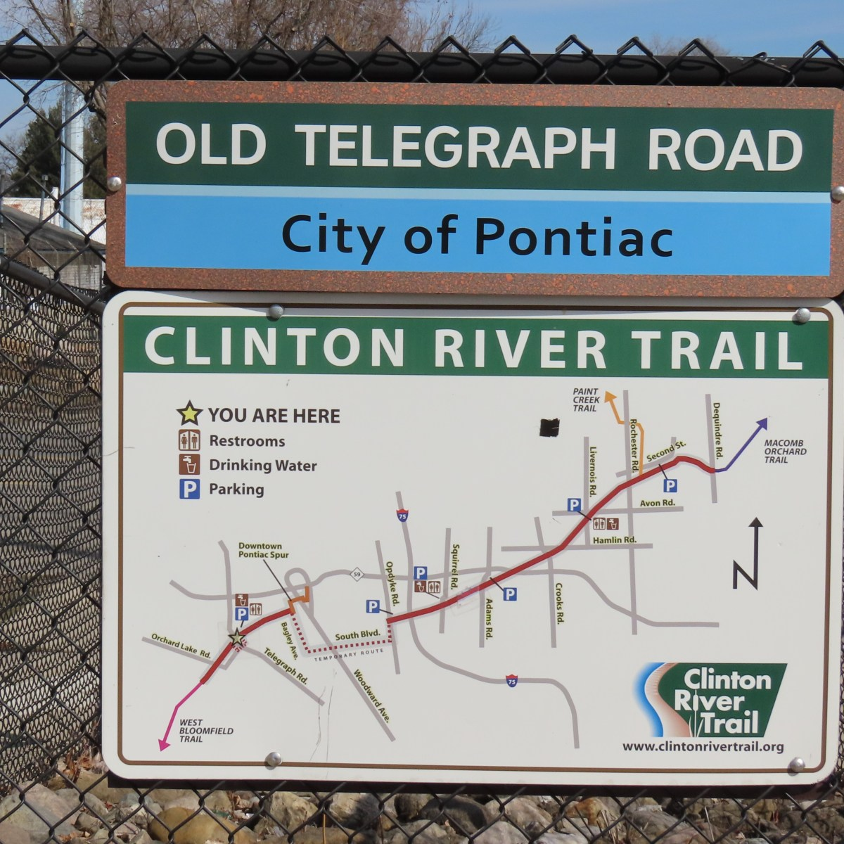 A map of the Clinton River Trail posted on a chain-link fence