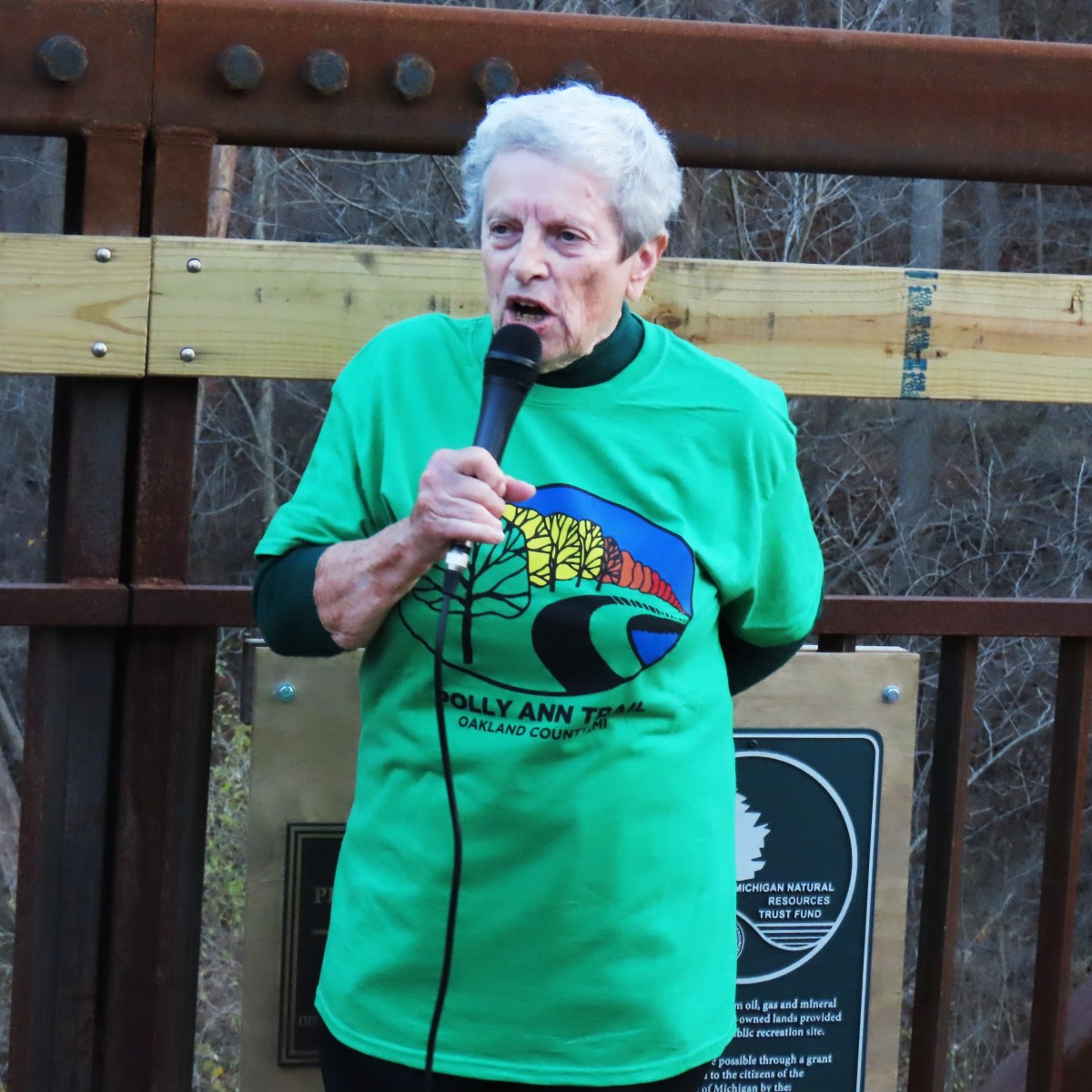 JoAnn Van Tassel speaks into a microphone at the bridge dedication