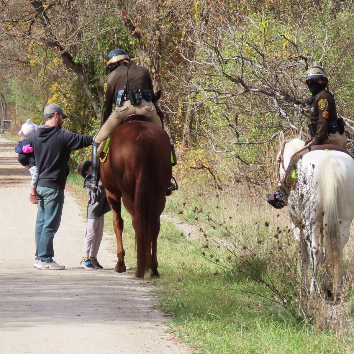 Two Sheriff Deputies on horseback stop to talk to a man and two young children on a trail
