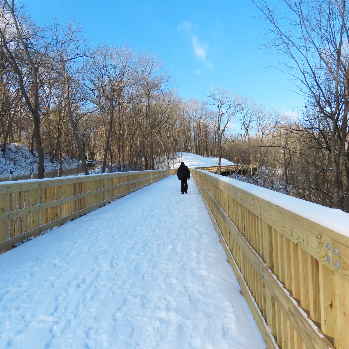 A person walks on a snowy boardwalk, facing away from the camera