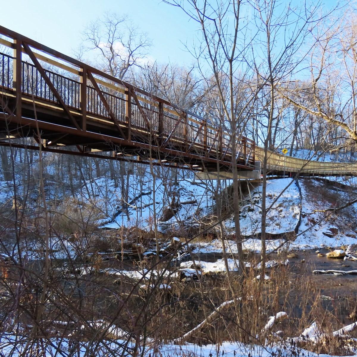 Steel bridge over wide creek in winter
