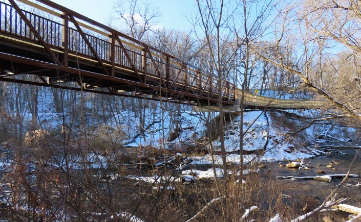 Steel bridge over wide creek in winter