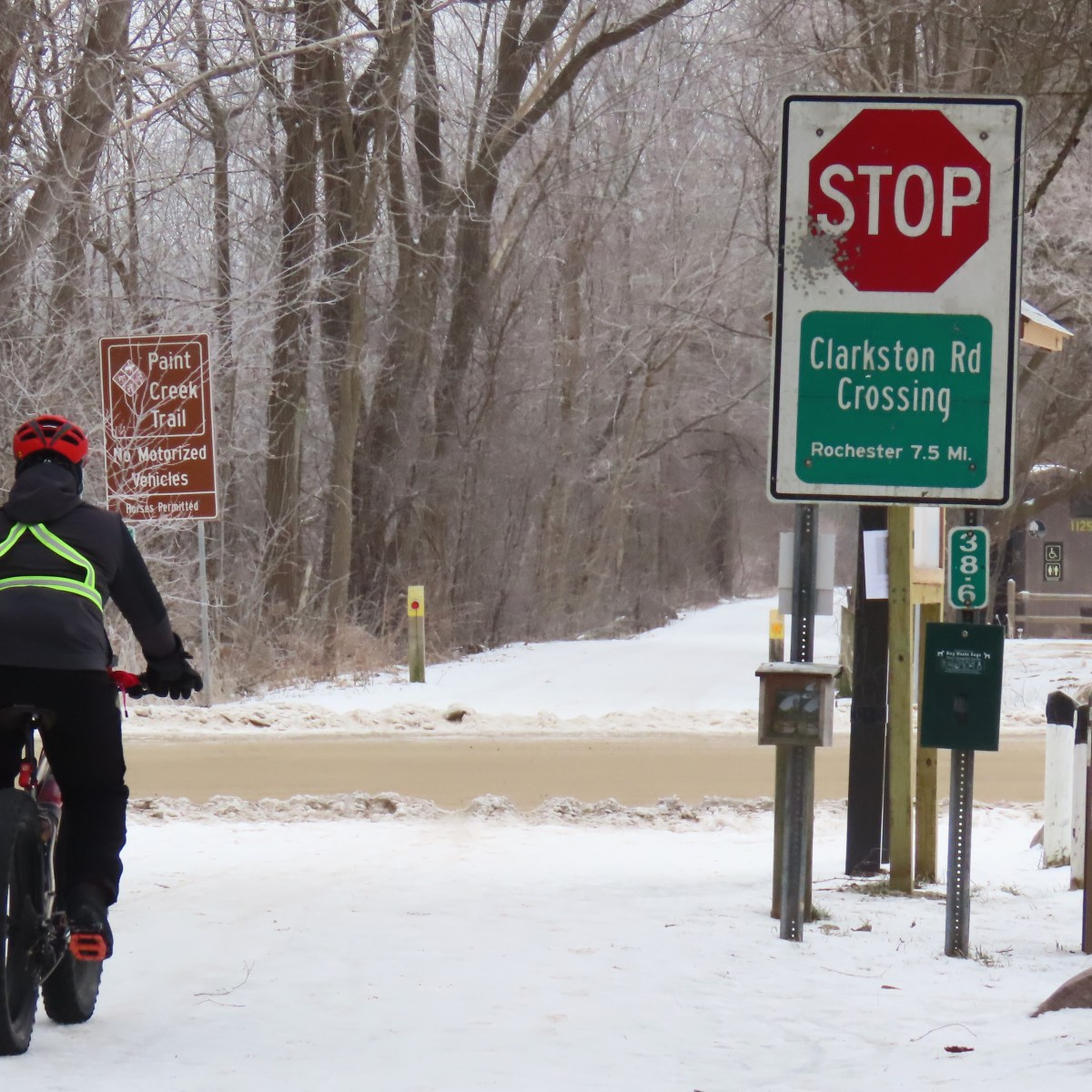 A person rides a fat tire bike on a snow-covered trail that intersects with a dirt road