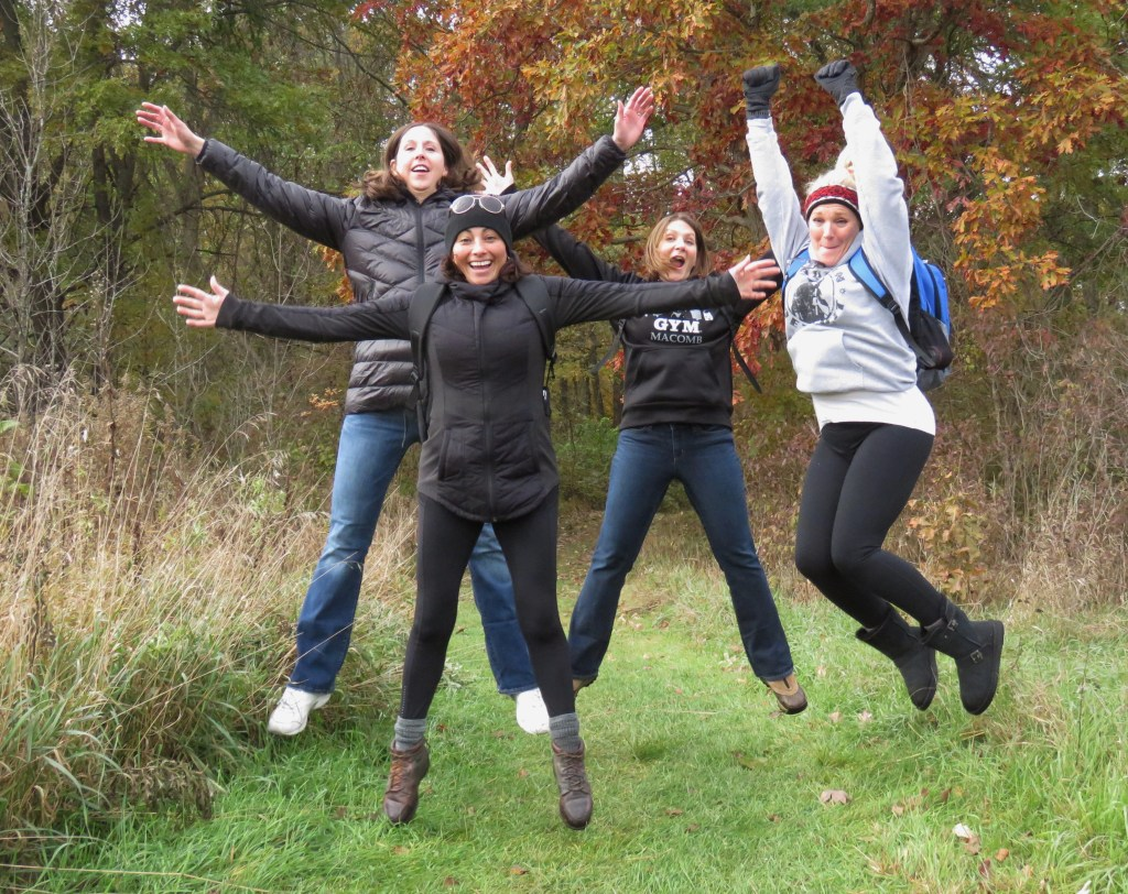 Four women jumping with outreached arms on a grassy trail in the autumn