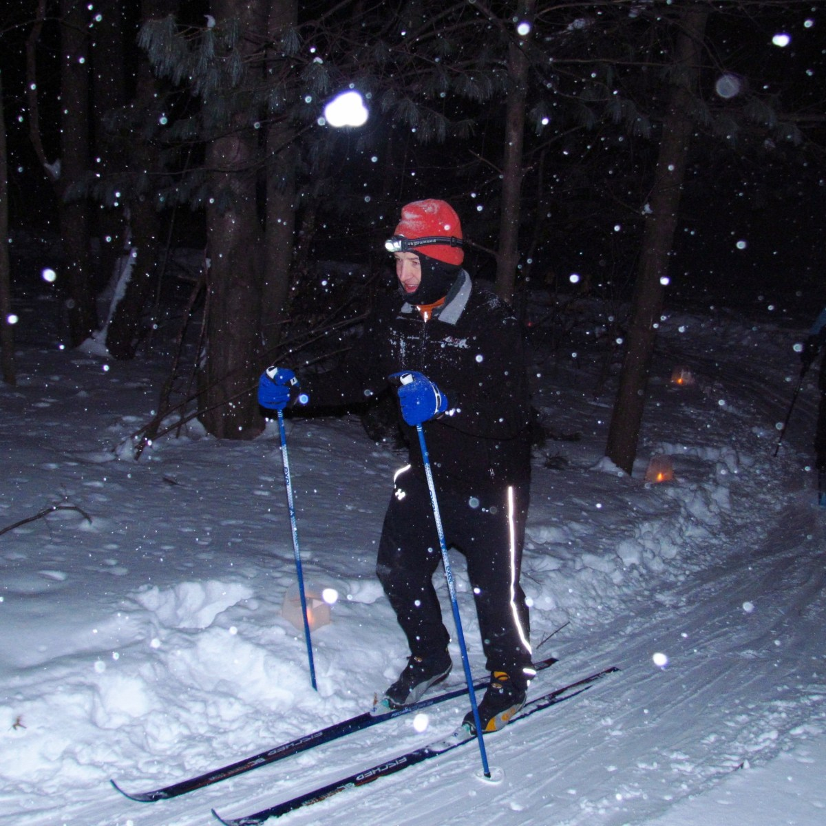 A pair of cross-country skiers ski in the dark night as snow falls