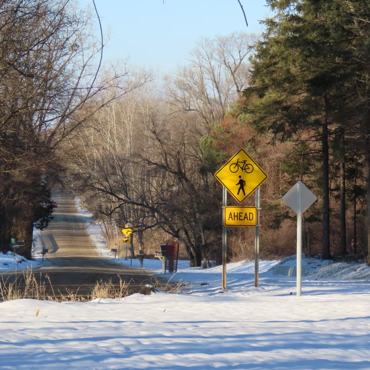 A dirt road cuts through a snow-covered path
