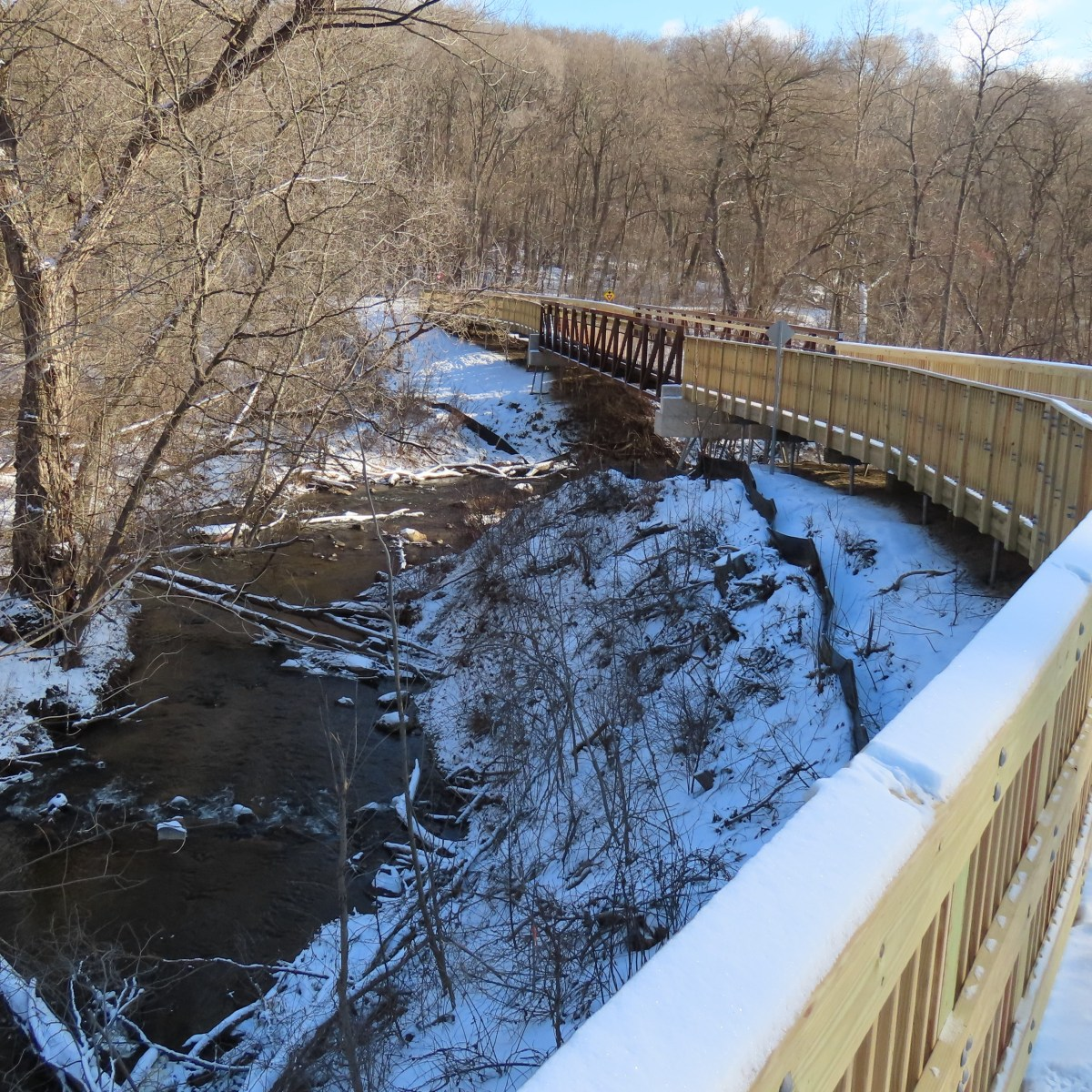 A snow covered boardwalk leading to a steel bridge over a creek