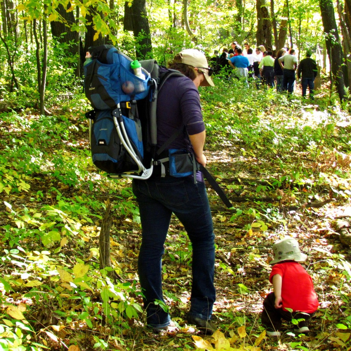 A woman wearing a hiking pack stands near a small child who has discovered something on the forest floor.