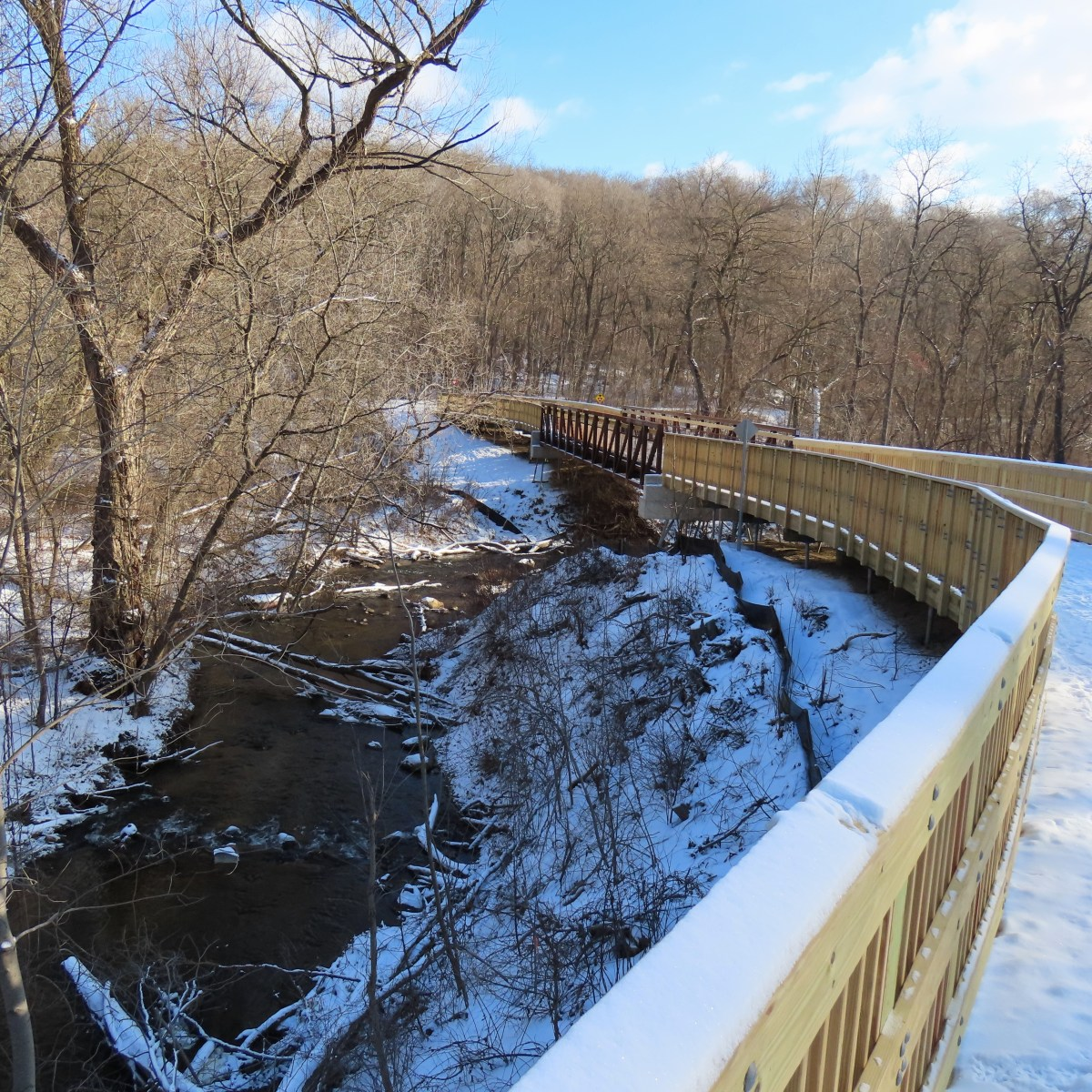 A wood-railed pedestrian bridge covered in snow