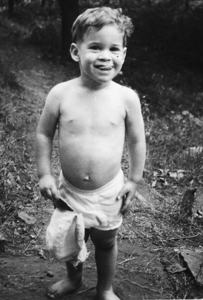 A black and white photo of a young boy standing outside, smiling, and dressed only in a diaper
