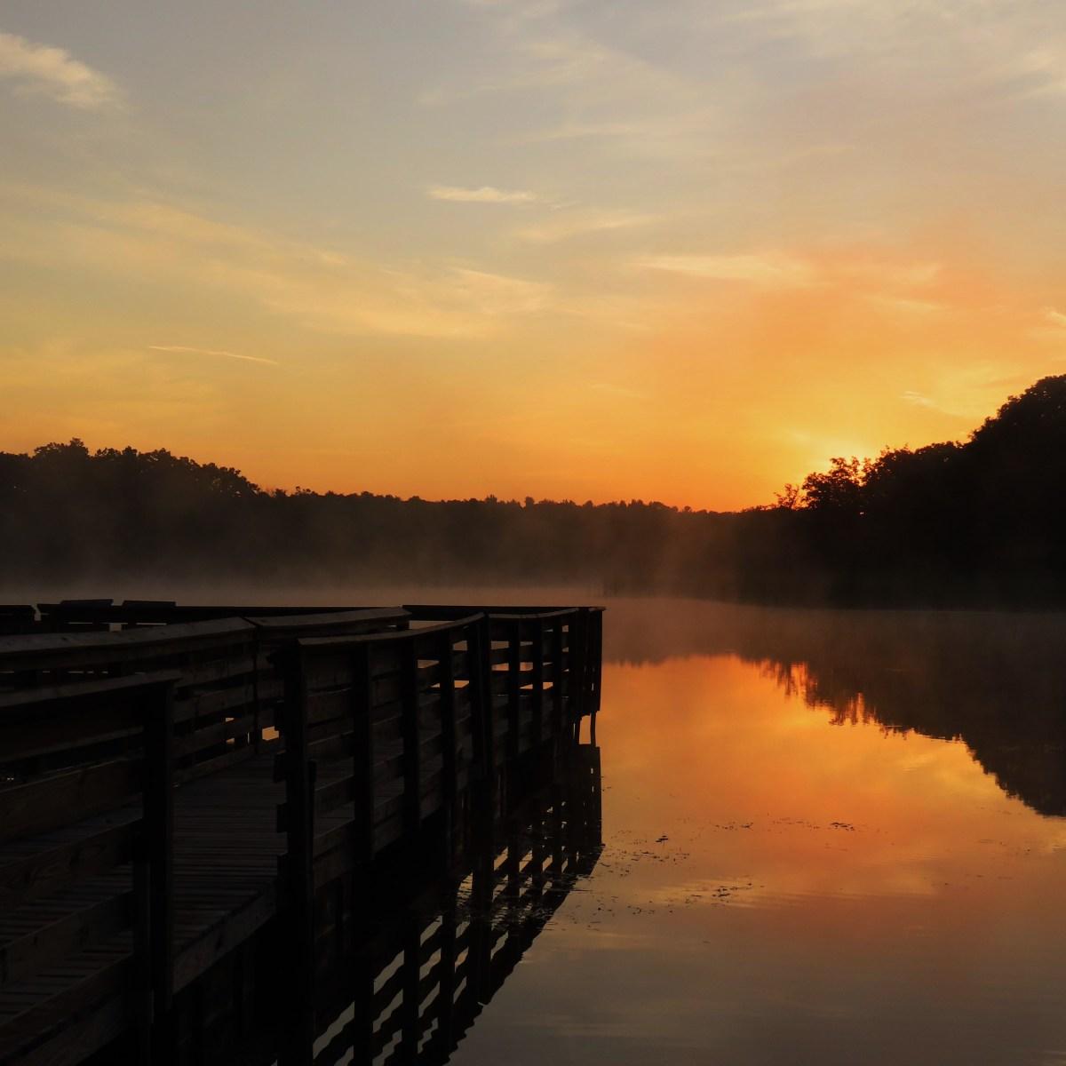 A golden sunrise reflects onto a misty lake