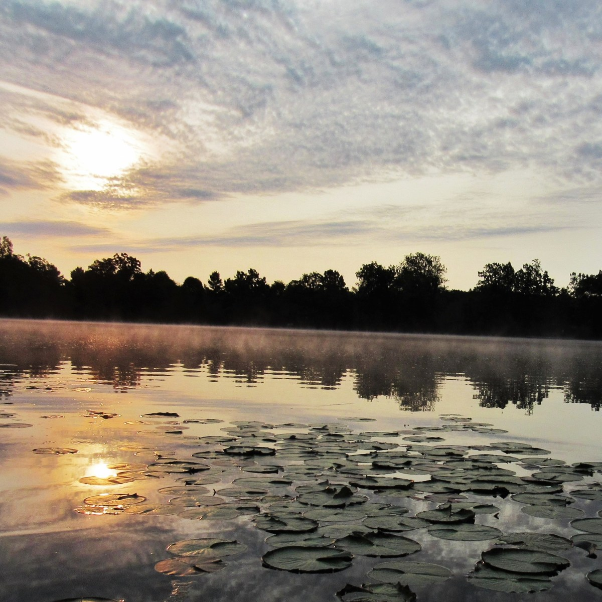 The sun and clouds reflect on a lake
