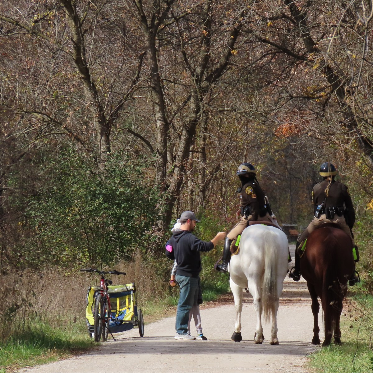A man and his children stop on a trail to speak to two deputies on horseback
